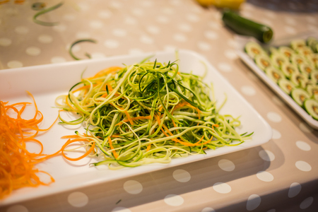 Strips of zucchini and carrots in a square white plate. Stock Photo