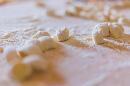 Handmade processing of dumplings above a wooden board.