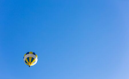 Yellow and blue hot air balloon in lonely flight in the blue sky.