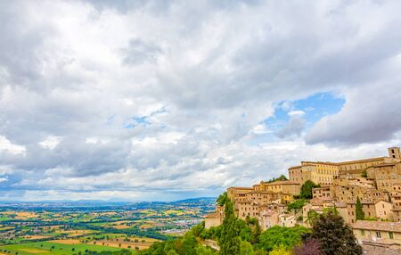 The town of Todi in Umbria in Italy with the surrounding countryside and the cloudy sky