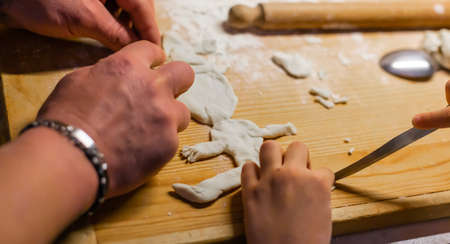 The hands of the child with the hands of the father on the table to knead the bread pass the time making molds in lockdown.