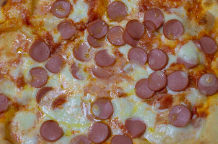 Red pizza with tomato sauce with mozzarella and frankfurters close up view.