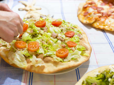 Hands of woman preparing homemade white pizza with salad, tuna and fresh tomatoes.