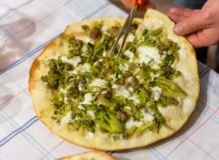Hands of man who with scissors cut white pizza with mozzarella, broccoli and sausage. Reklamní fotografie