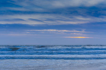 The rough sea at sunset seen from the beach in winter. Stok Fotoğraf