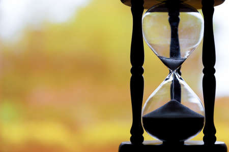 Hourglass silhouette with yellow background. Stok Fotoğraf
