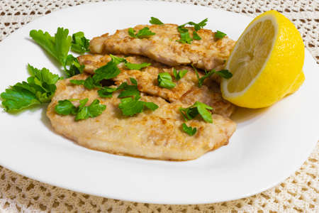 Pork escalopes in a white plate with half a lemon and parsley on an embroidered crochet tablecloth.