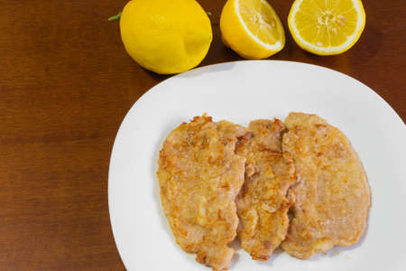 Three pork escalopes in a white plate and two lemons on a brown wooden table.