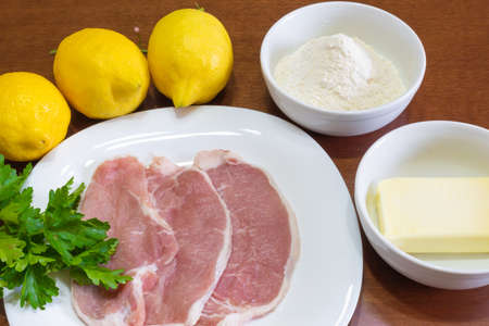 Ingredients for the preparation of lemon escalopes with butter, parsley and flour. Above a wooden table.