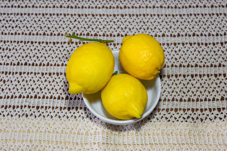 Three lemons in a white bowl on top of an embroidered crochet tablecloth seen from above.