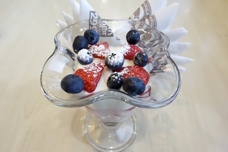 Berry dessert of sweet yogurt with cheese, berries, strawberry syrup and powdered sugar Banco de Imagens
