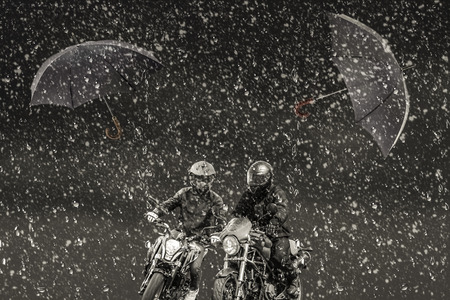 unnecessary: Through snow and rain rushing two motorcyclists. In the background they fly unnecessary two umbrellas. Stock Photo