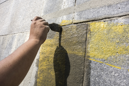 Man with the help of a wet brush erases the graffiti painted on the wall. Preparation of the surface before finishing the paint. Repair of the premises. Rough wall finishing. Stock Photo