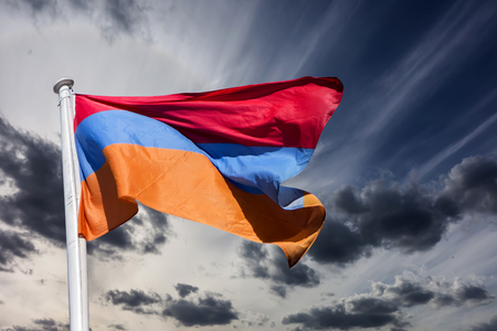 Armenian flag against the background of halo and thunderclouds. Stock Photo