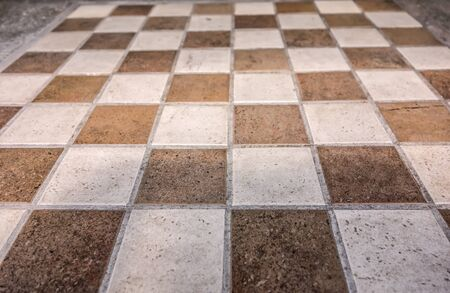 Vintage stone table for playing checkers or chess, with a chessboard lined with marble tiles outdoor.