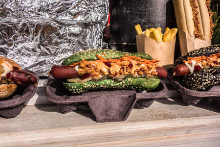 Hot dogs on a wooden table on the background of the oven and foil closeup. Street food of rustic style.