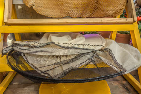 Beekeeper's protective clothing, honeycomb and wax beautiful yellow rustic background