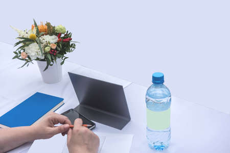 Business background with human hands holding a pen over a piece of paper. On the white table are a telephone, a bottle of clean drinking water, a diary and a bouquet of flowers. Planning for the future year, new plans, business plan for women.