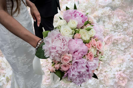 Wedding bouquet in the hands of the bride close-up. Natural pink and white flowers of roses and peonies. Figures of the bride in a wedding dress and the groom on a beautiful background of a panel of roses.