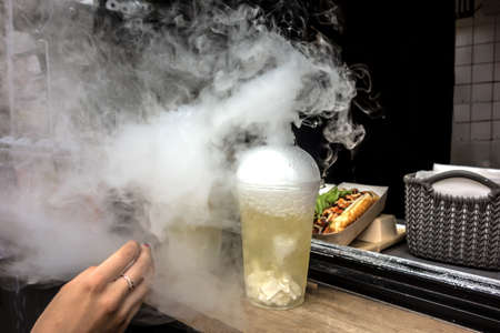 Classic alcohol cocktail with smoke. A woman's hand is outstretched to a cocktail with smoke. Young girl wants to freshen up Foto de archivo