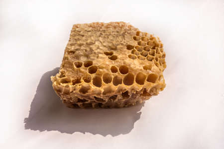 Piece of honeycomb with natural honey and natural shadows isolated on a white background. Beekeeping products sold in the food market, used in homeopathy, diet and cosmetology. Hexagonal honeycomb structure. Foto de archivo