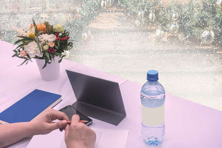 New Year business background for planning future affairs. Hands with a pen, a mobile phone, a diary, a bottle of clean water and a bouquet of flowers against the background of a Christmas tree with garlands. Foto de archivo