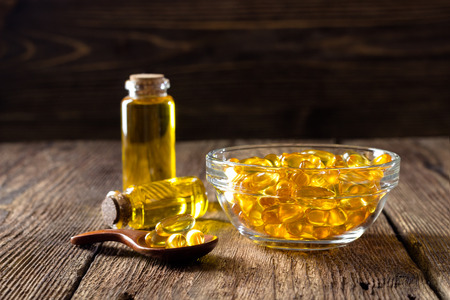 Fish oil capsules on wooden background, vitamin D supplement Imagens