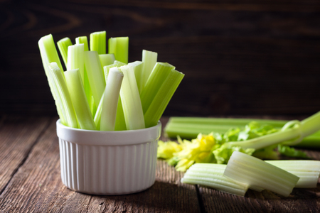 Sliced celery in a white bowl on a wooden background Stockfoto