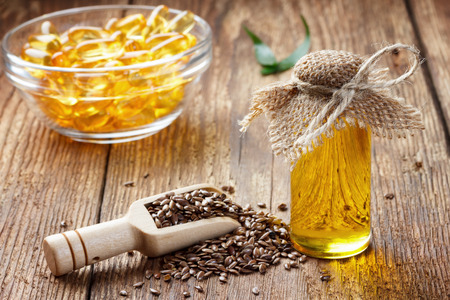 Flax seeds and oil in bottle on wooden background Zdjęcie Seryjne