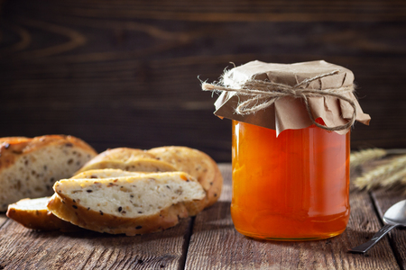 Jar with apricot jam on wooden table Stockfoto