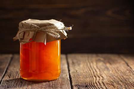 Jar with apricot jam on wooden table Banco de Imagens