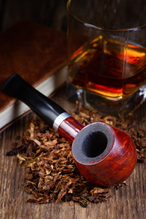 Lacquered smoking pipe, tobacco pile and alcohol drink on vintage wooden table. Stockfoto