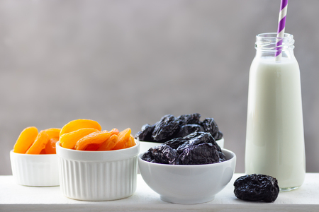 Concept healthy food, vegetarianism, diet. Yogurt, dried apricots and prunes in a white bowls.