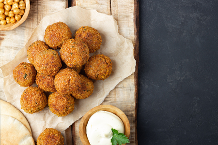 Vegetarian chickpeas falafel balls on wooden rustic board. Traditional Middle Eastern and arabian food. Dark background. Copy space.