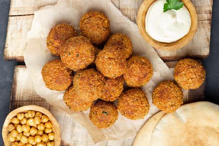 Vegetarian chickpeas falafel balls on wooden rustic board. Traditional arabian food. Dark background. Reklamní fotografie