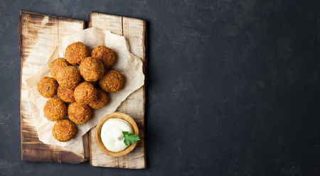 Vegetarian chickpeas falafel balls on wooden rustic board. Traditional Middle Eastern and arabian food. Dark background. Copy space. Stock Photo
