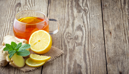 A glass cup of tea with lemon, mint and ginger on wooden rustic table. 版權商用圖片