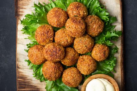 Vegetarian chickpeas falafel balls on wooden rustic board. Traditional arabian food. Dark background.
