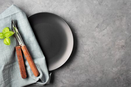 Table setting. Black plate, cutlery and napkin over gray concrete background.
