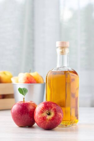 Healthy organic food. Apple cider vinegar or juice in glass bottle and fresh red apples on a light background.