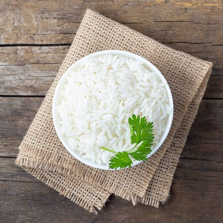 Boiled rice in a bowl on wooden rustic table.