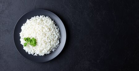 Steamed rice on black plate. Black stone background. Top view with copy space. Фото со стока