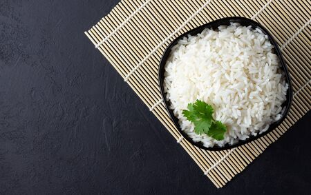 Steamed rice on black plate over bamboo tablecloth. Black stone background. Top view with copy space.