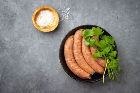 Raw uncooked meat sausages in a black iron pan. Top view with copy space. Gray concrete background.