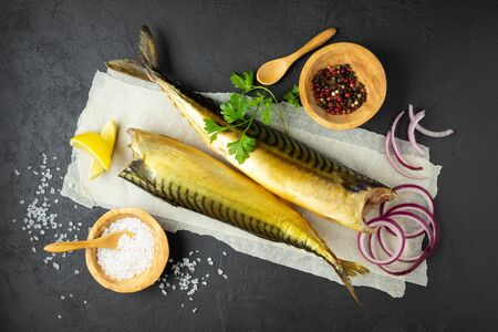 Smoked fish mackerel or scomber on a white parchment paper. Black or dark stone background. Top view. Фото со стока