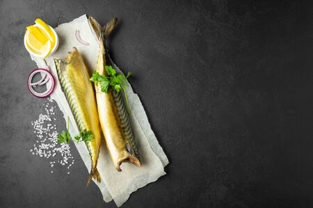 Smoked fish mackerel or scomber on a white parchment paper. Black or dark stone background. Top view with copy space.