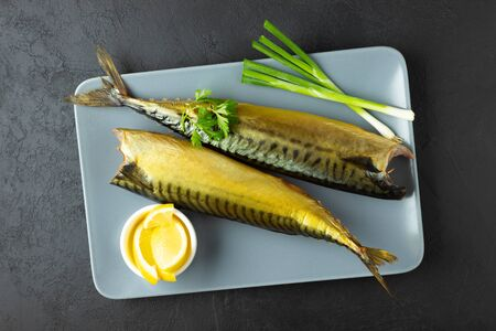 Smoked fish mackerel or scomber on a rectangular plate. Black or dark stone background. Top view.