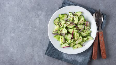 Fresh cucumber salad with flax seeds on gray stone background. Top view.