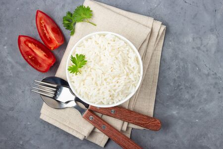 Boiled rice and cutlery in a bowl. Gray stone background. Top view.
