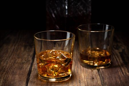 Two glass of whiskey with ice and crystal decanter on wooden table.